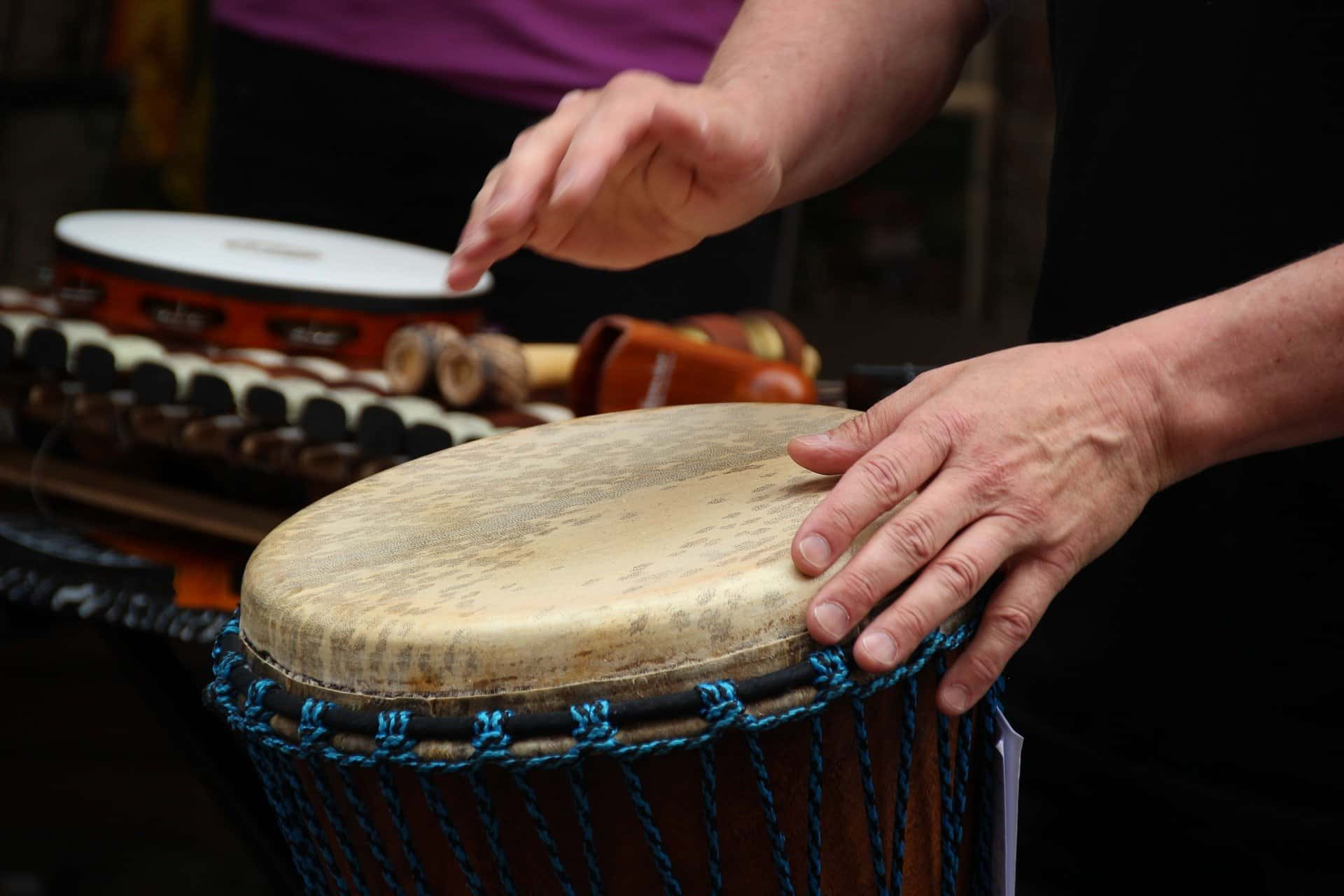 person playing a djembe drum