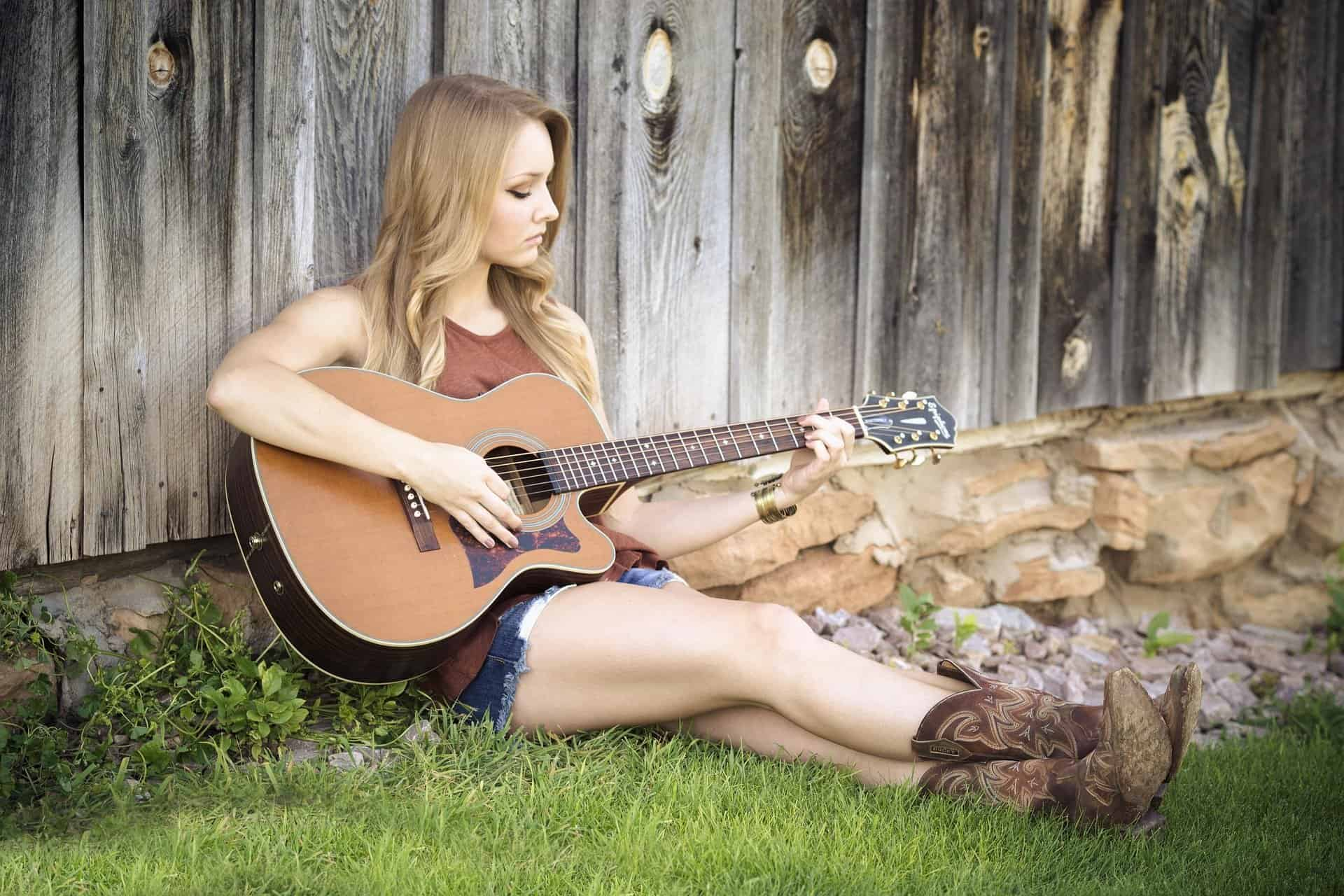 a girl playing guitar outside