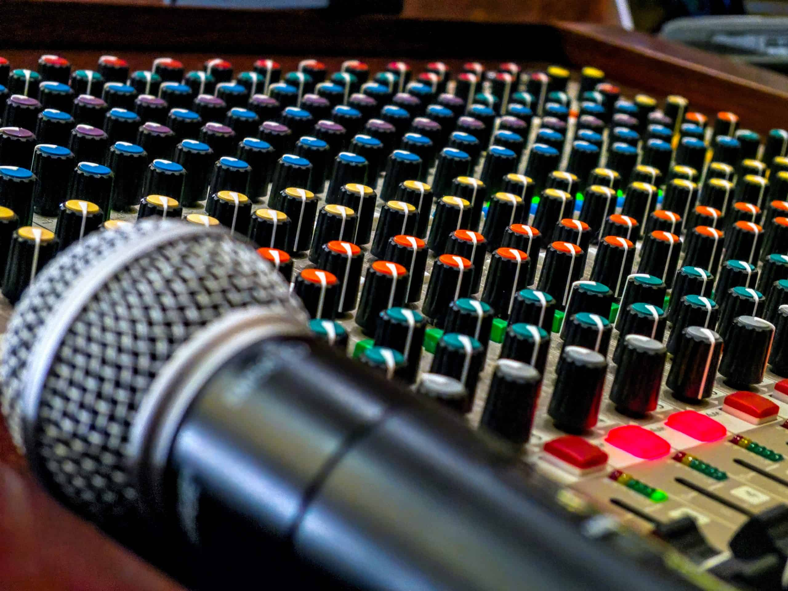 A microphone rests on a live sound mixing board containing colorful knobs.