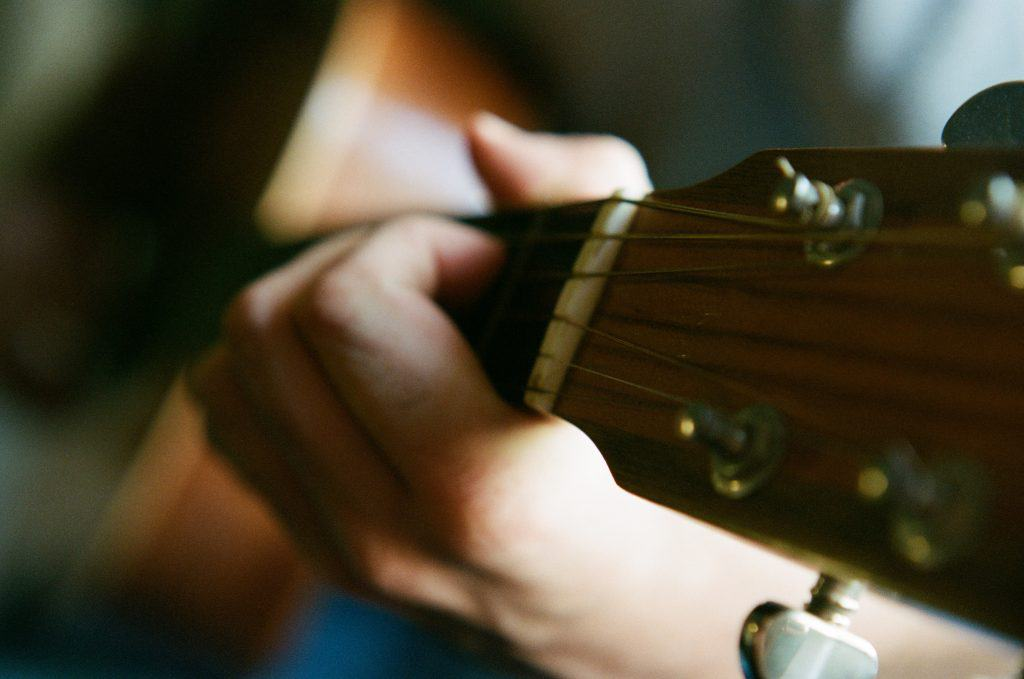 selective focus photography of person playing guitar