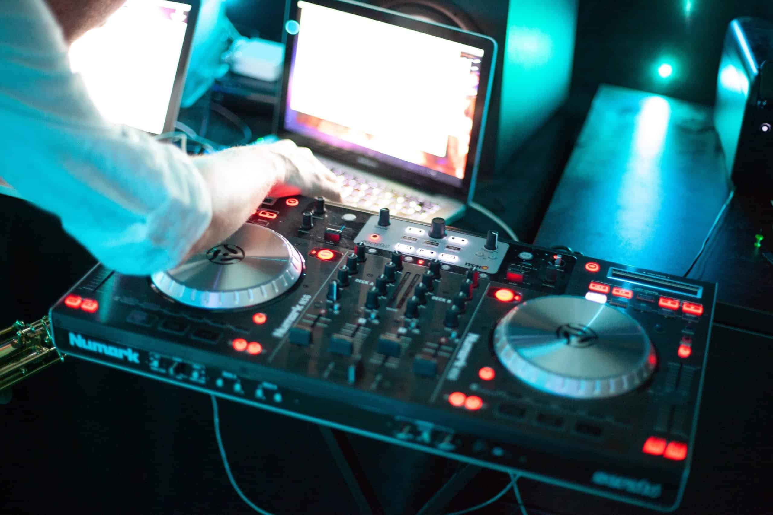 A DJ sets up his mixing table for a night filled with music.