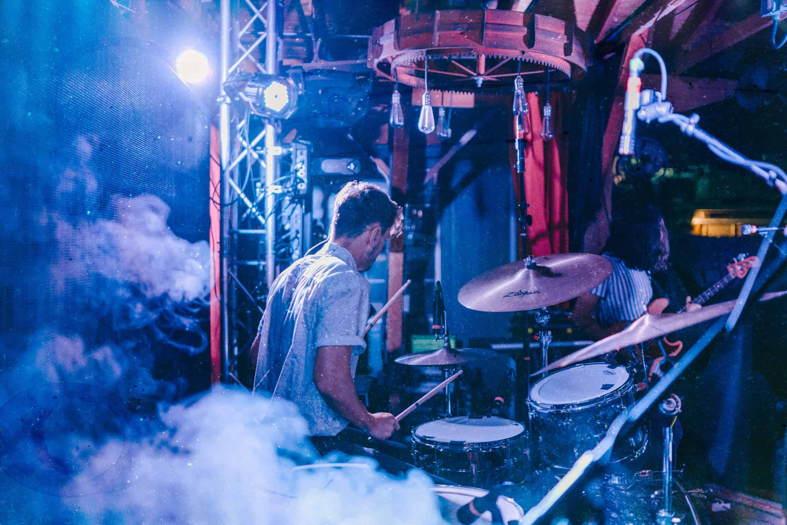 selective focus photography of man playing drum