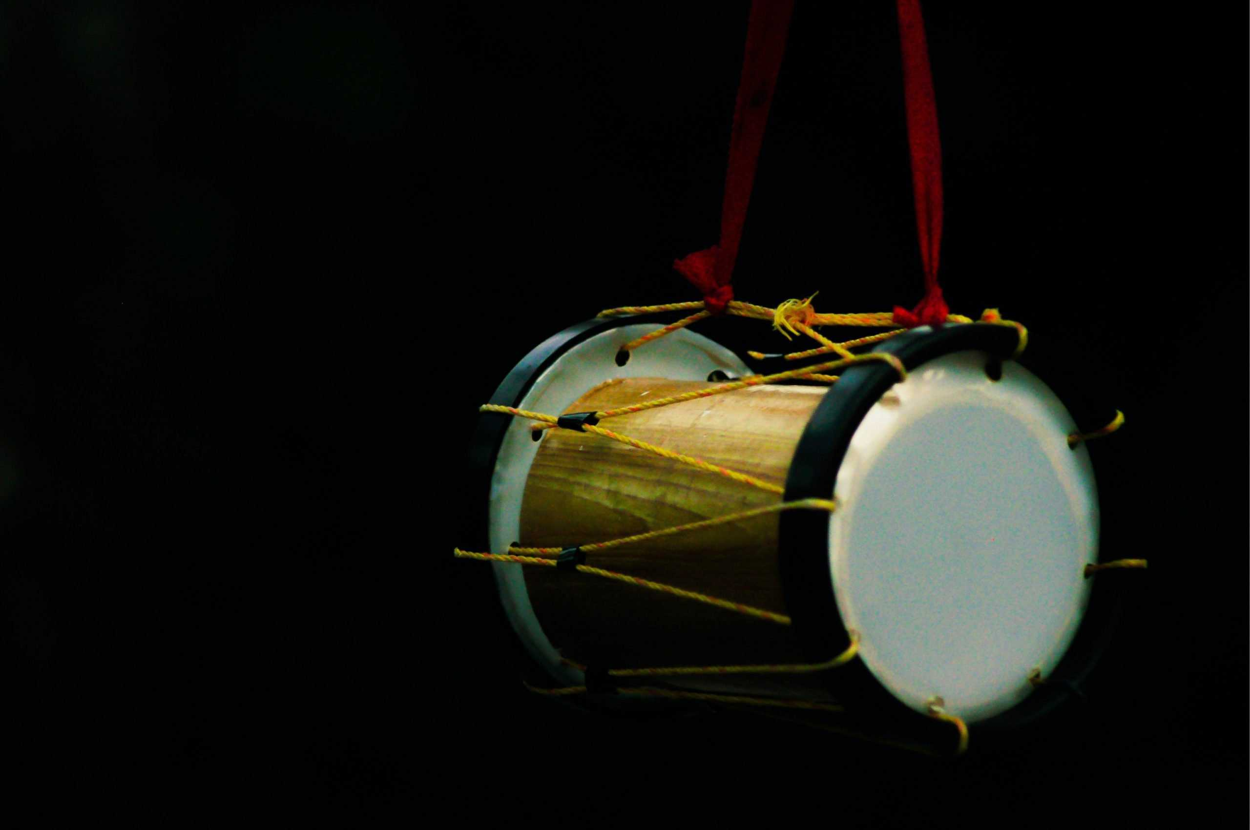 white and brown drum with red strap